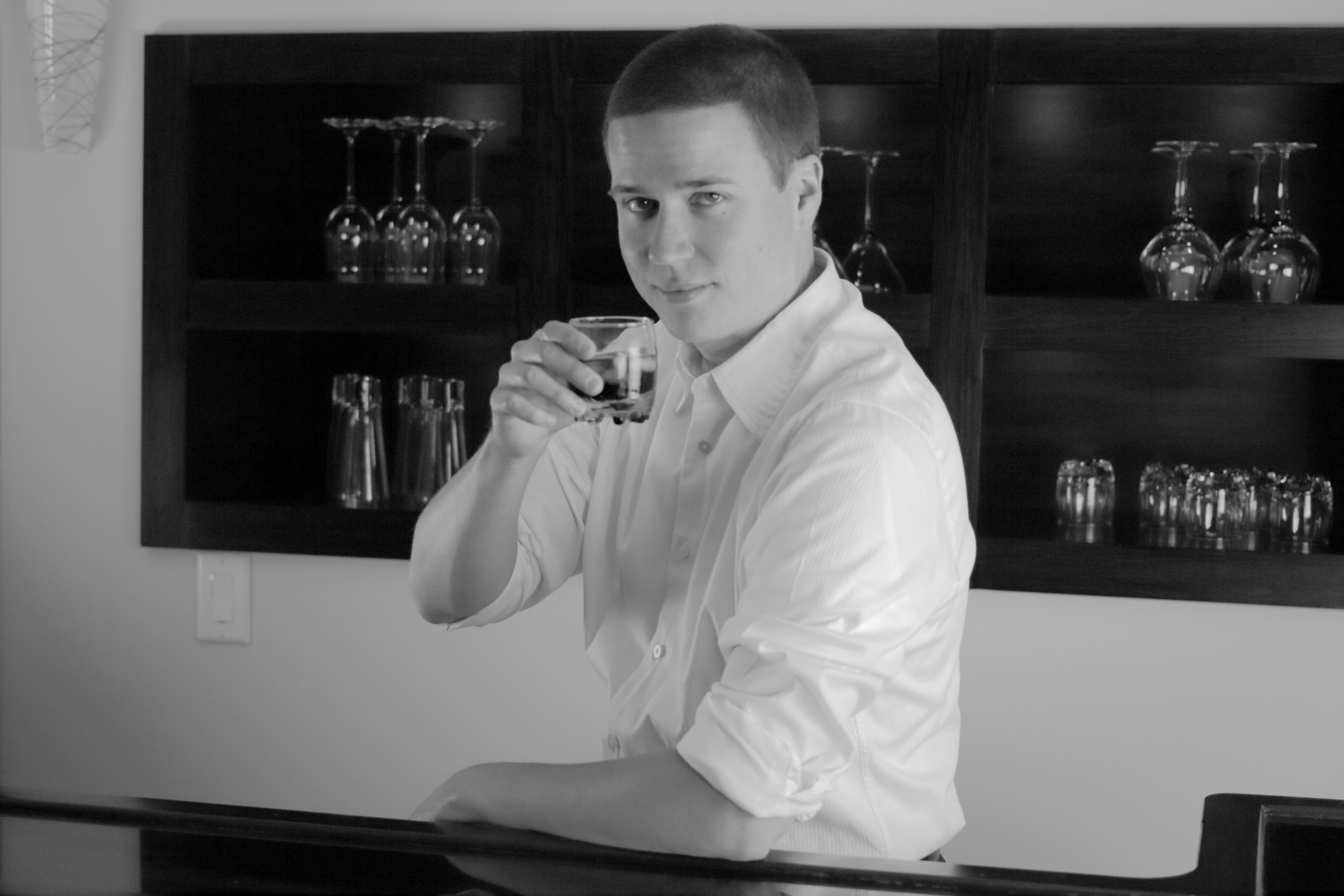 The author stands behind a bar wearing a formal white shirt  				with the collar unbuttoned and the sleeves rolled up. As his  				eyes meet the camera, he smirks and hoists a tumbler half full  				of dark liquid.